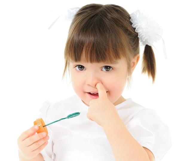 Ragazza carina in abito bianco festivo tiene le bolle di sapone nelle mani. il bambino distoglie lo sguardo, sfondo chiaro