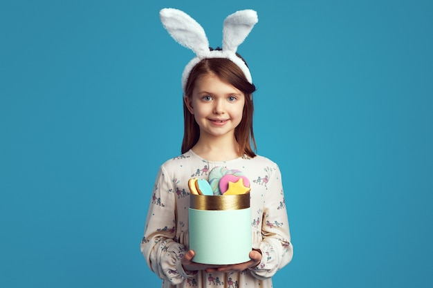 Ragazza carina che tiene una scatola con biscotti con orecchie da coniglio e vestito carino
