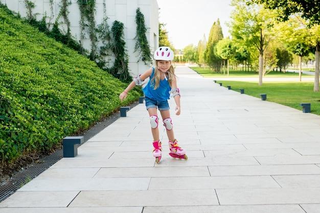 Ragazza carina che impara a guidare i rollerblades sul parco pubblico in giornata di sole