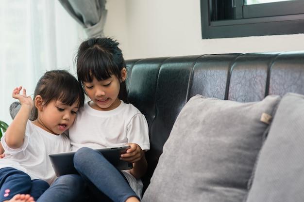 Ragazza carina che guarda sua sorella minore che sta giocando su uno smartphone