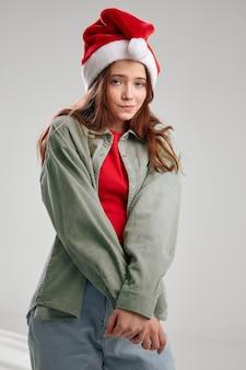 Ragazza carina in un cappello da festa e giacca su uno sfondo grigio