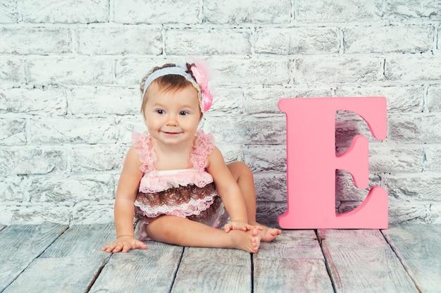 Ragazza carina in abito rosa con la lettera e
