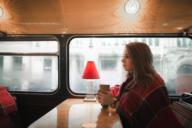 Ragazza carina in plaid si siede in un accogliente bar con una tazza di bevanda calda in mano