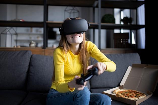 La ragazza carina gioca sulla console e mangia la pizza. esperienza vr