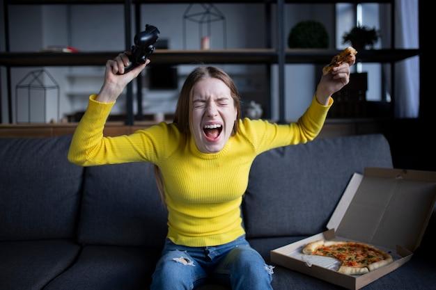 La ragazza carina gioca sulla console e mangia la pizza