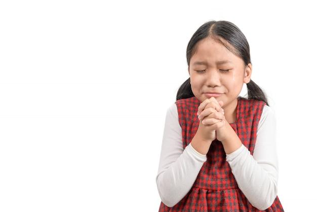 Ragazza sveglia che prega e grida isolato su fondo bianco.