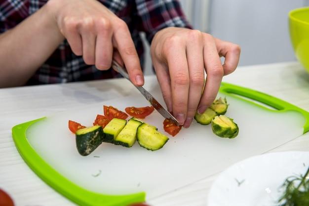 La ragazza carina prepara un'insalata di verdure e verdure diverse per uno stile di vita sano