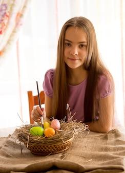Ragazza carina che si prepara per la pasqua e dipinge le uova