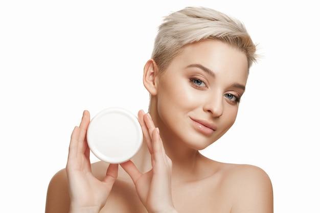 Ragazza carina che si prepara per iniziare la sua giornata. sta applicando la crema idratante sul viso. la cura, la pelle, il trattamento, la salute, la spa, il concetto cosmetico