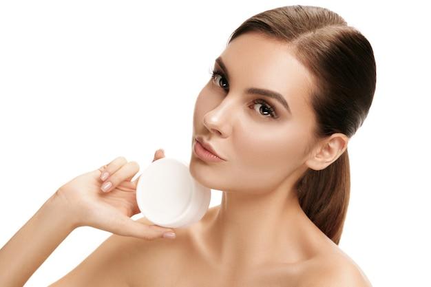 Ragazza carina che si prepara a iniziare la sua giornata. sta applicando la crema idratante sul viso in studio. il concetto di bellezza, cura, pelle, trattamento, salute, spa, cosmetico e pubblicitario