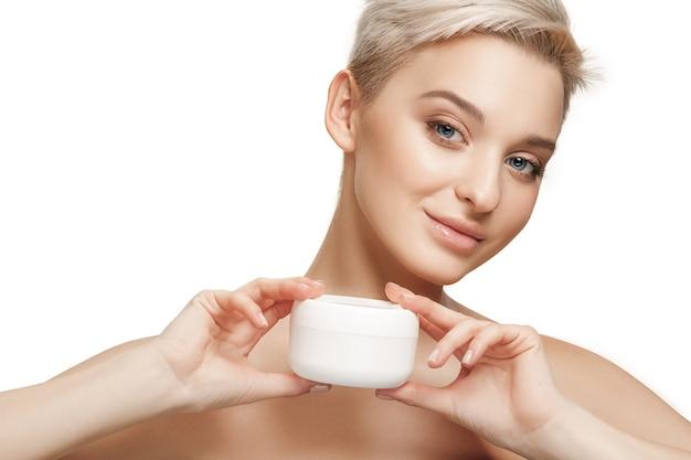 Ragazza carina che si prepara a iniziare la sua giornata. sta applicando la crema idratante sul viso in studio. la cura, la pelle, il trattamento, la salute, la spa, il concetto cosmetico