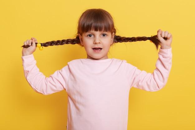 La ragazza sveglia tira le sue trecce da parte a mano, con la bocca aperta, bambino femminile caucasico in camicia rosa pallido contro il muro giallo