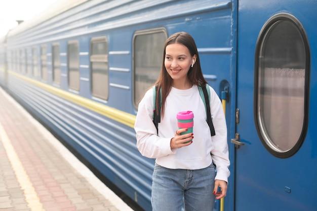 Ragazza carina alla stazione ferroviaria tenendo il caffè
