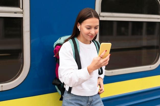 Ragazza carina alla stazione ferroviaria utilizzando il telefono cellulare