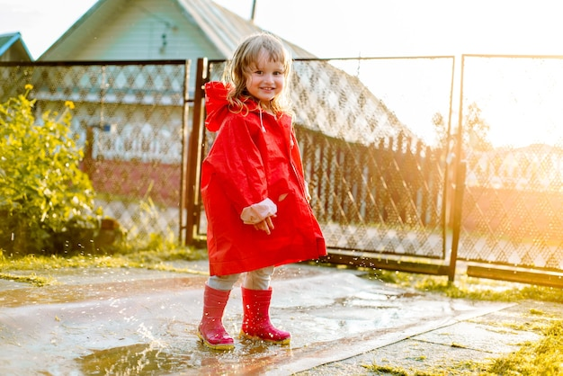Ragazza carina in una giacca rossa sta saltando nella pozzanghera. il caldo sole autunnale o estivo. estate in villaggio.
