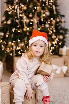 Ragazza carina in cappello della santa con regalo di natale su sfondo albero di natale. bambino con regalo di natale a casa.