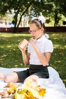 Una studentessa carina beve il succo con una cannuccia da una tazza ecologica durante un picnic su una coperta nel parco. pasti scolastici. vista verticale