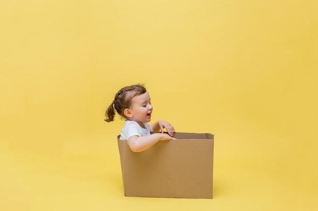 Una ragazza carina si siede in una scatola di cartone e distoglie lo sguardo. una bambina in una maglietta bianca su uno spazio giallo. consegna senza contatto