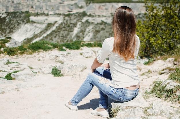 La ragazza carina si siede sul pendio della montagna chufut-kale in jeans strappati