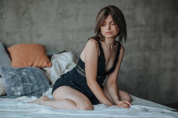 Ragazza carina seduta sul letto al mattino in lingerie nera