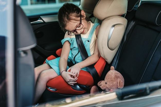 Ragazza carina seduta in un'auto su un seggiolino per auto di sicurezza.