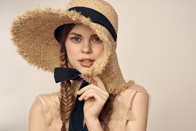 Ragazza carina in cappello di paglia con nastro nero e vestito su beige