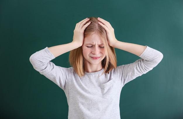 Ragazza carina che soffre di mal di testa sulla parete colorata