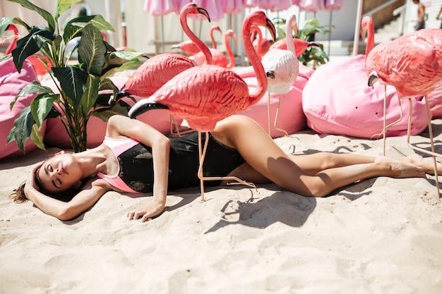 Ragazza carina in costume da bagno alla moda sdraiata sulla sabbia mentre chiude gli occhi sognante con fenicotteri rosa artificiali e grandi cuscini vicino sulla spiaggia. ritratto di premurosa signora sdraiata sulla sabbia e prendere il sole