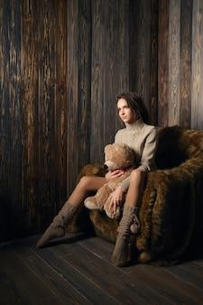 Ragazza carina in calde calze al ginocchio e maglione con orsacchiotto tra le gambe.