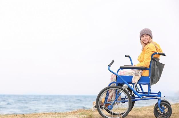 Ragazza carina in sedia a rotelle sulla riva del mare