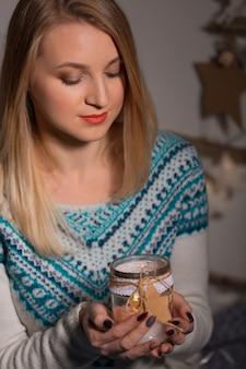Una ragazza carina in un maglione lavorato a maglia bianco si siede con una candela in mano