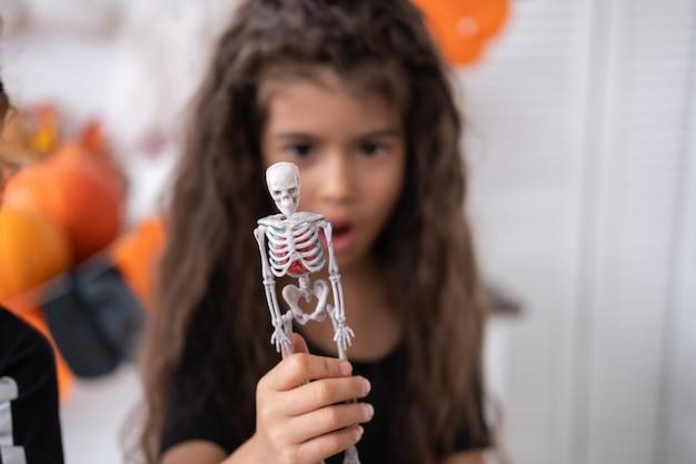Ragazza carina in costume da strega strega che si diverte in cucina, gioca con lo scheletro, festeggia halloween. messa a fuoco selettiva.