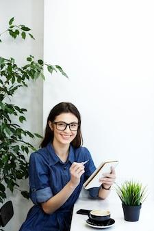 Ragazza carina con i capelli neri che indossa camicia blu spogliata e occhiali da vista seduti nella caffetteria con il telefono cellulare e la tazza di caffè, concetto di freelance, ritratto, ascolto di musica, svernamento e sorridente.