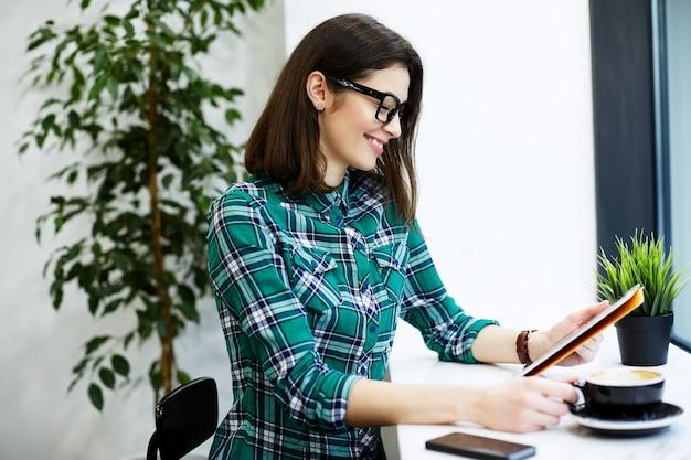 Ragazza carina con i capelli neri che indossa camicia e occhiali da vista seduti nella caffetteria con tablet e tazza di caffè, concetto freelance, guardando tablet.