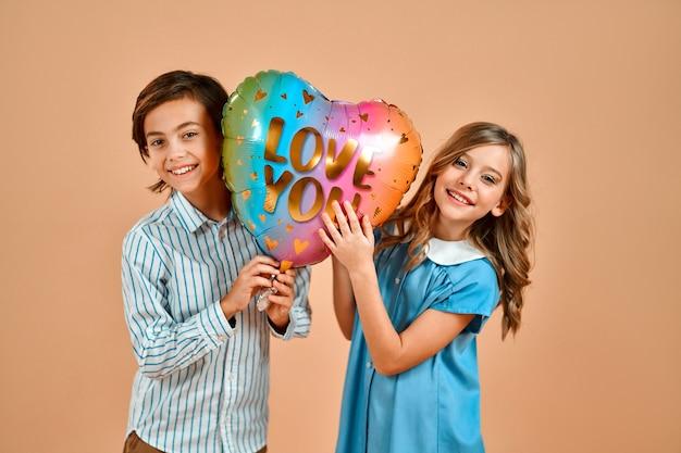 Una ragazza carina con i riccioli in un vestito blu e un bel ragazzo con una maglietta tengono in mano un palloncino con le parole
