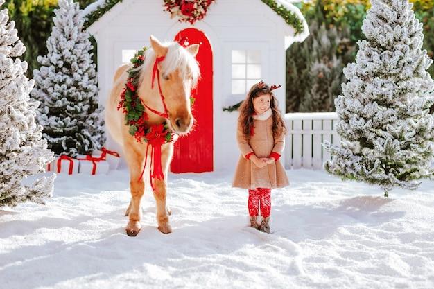 Ragazza carina con corna di cervo in piedi con un cavallo pony sotto la neve