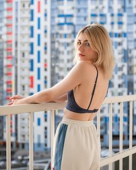 Una ragazza carina con le lentiggini in un top di pizzo viola e pantaloni della tuta in piedi sul balcone