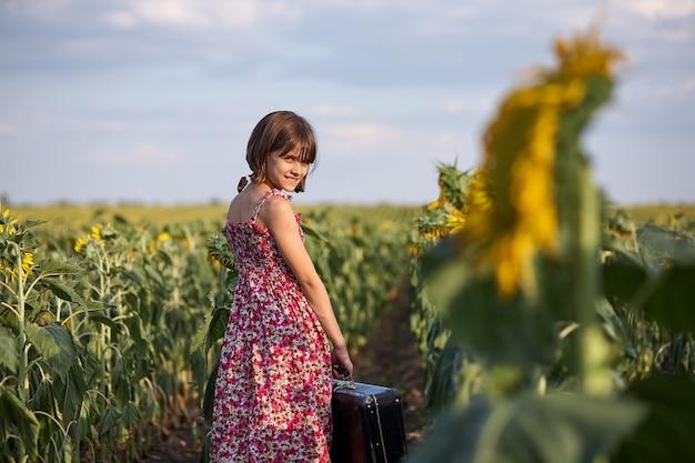 Ragazza carina con la vecchia valigia in un campo di girasoli.