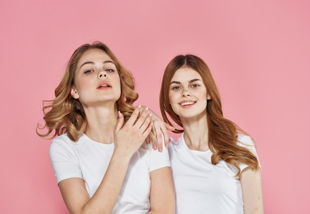 Amiche carine in magliette bianche abbracciano lo stile di vita dei vestiti alla moda