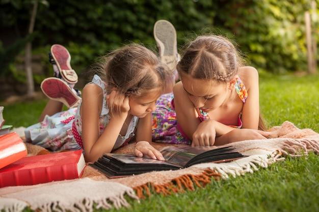 Ragazze carine sdraiate sull'erba al parco e guardando vecchie foto di famiglia