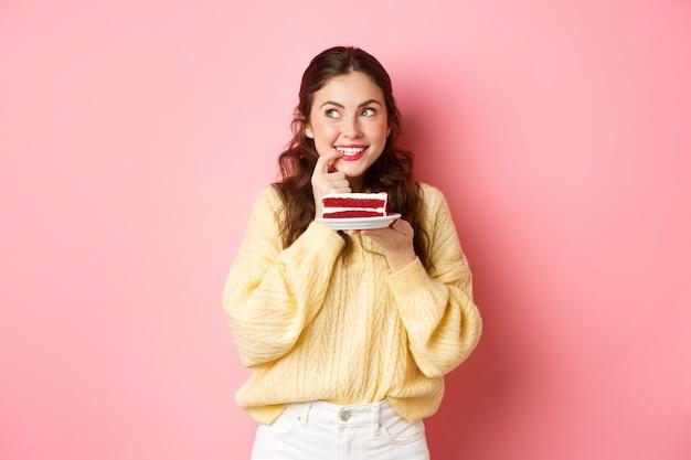 Ragazza carina glamour pensando e guardando da parte vuole provare una deliziosa torta tenendo il piatto con il dessert e sorridente in piedi contro il muro rosa