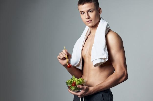 Ragazzo carino con un asciugamano sulle spalle dieta post allenamento sfondo isolato.