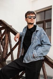 Modello carino bel giovane con acconciatura in abiti alla moda in posa in piedi su una scala in legno d'epoca in città hipster ragazzo urbano in occhiali da sole in una giacca di jeans si rilassa all'aperto.