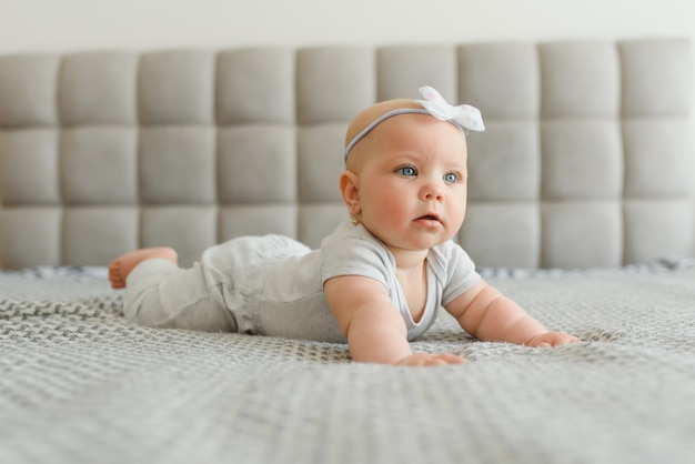 Bambina felice di 7 mesi sveglia in pannolino che si trova e gioca