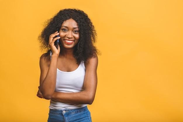 Ragazza nera afroamericana felice carina in casual parlando sul cellulare e ridendo
