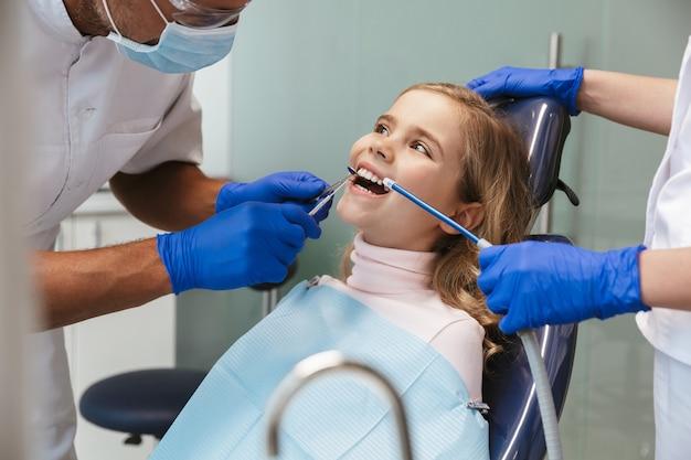 Ragazza carina felice bel bambino seduto nel centro medico dentista