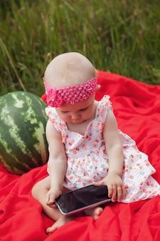 Bionda felice sveglia con la ragazza degli occhi azzurri 8 mesi in erba con l'anguria ed il telefono. concetto di alimentazione sana, infanzia, maturazione dei frutti, genitorialità, raccolto stagionale. perfetto bambino caucasico in natura