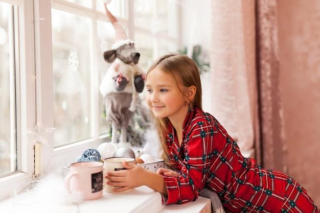 Carina ragazza felice in pigiama scozzese mangia marshmallow, guardando la telecamera a natale