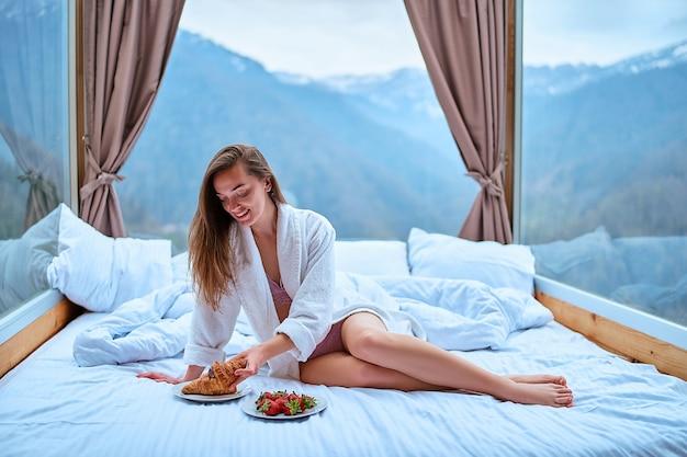 Carino felice splendida sonnolenta risveglio donna con gambe lunghe e sottili che indossa accappatoio seduto sul letto bianco in camera d'albergo con grandi finestre durante la colazione mattutina. inizio inizio nuovo giorno