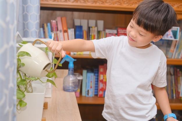 Simpatico bambino asiatico felice che innaffia le piante con l'annaffiatoio imparando a casa